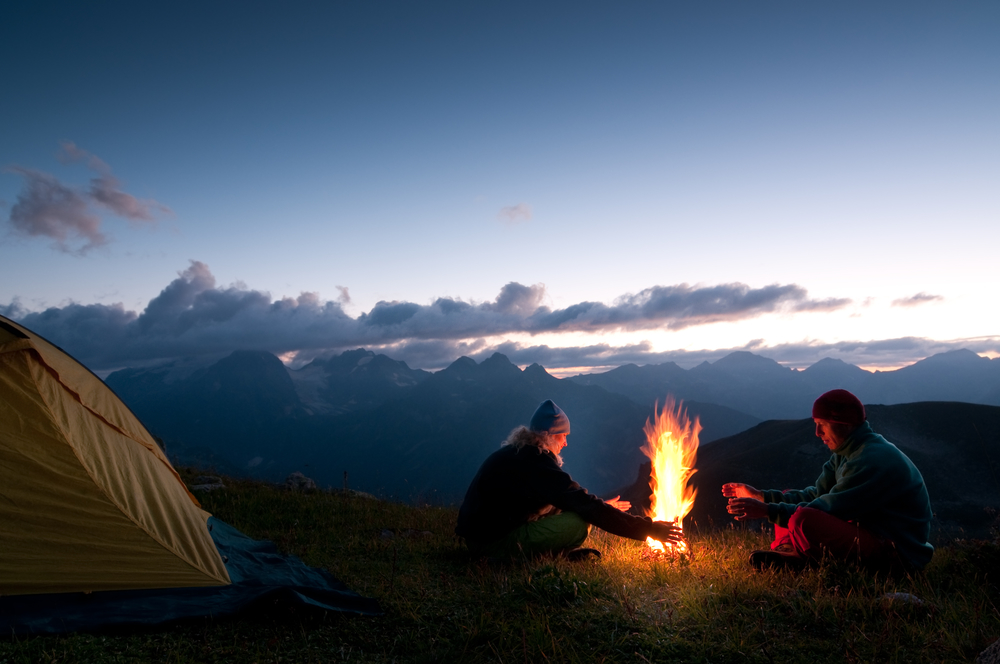 Couple by a fire camp in the wilderness